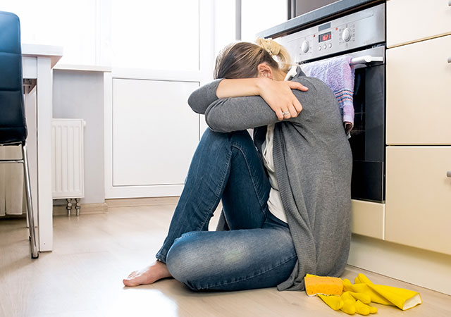 woman upset kitchen yellow gloves