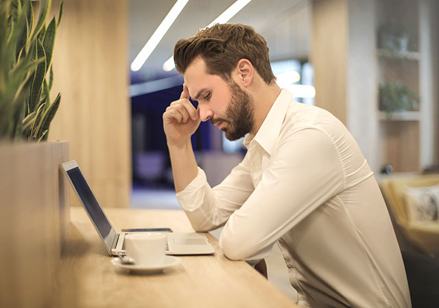 man holding head looking at laptop screen