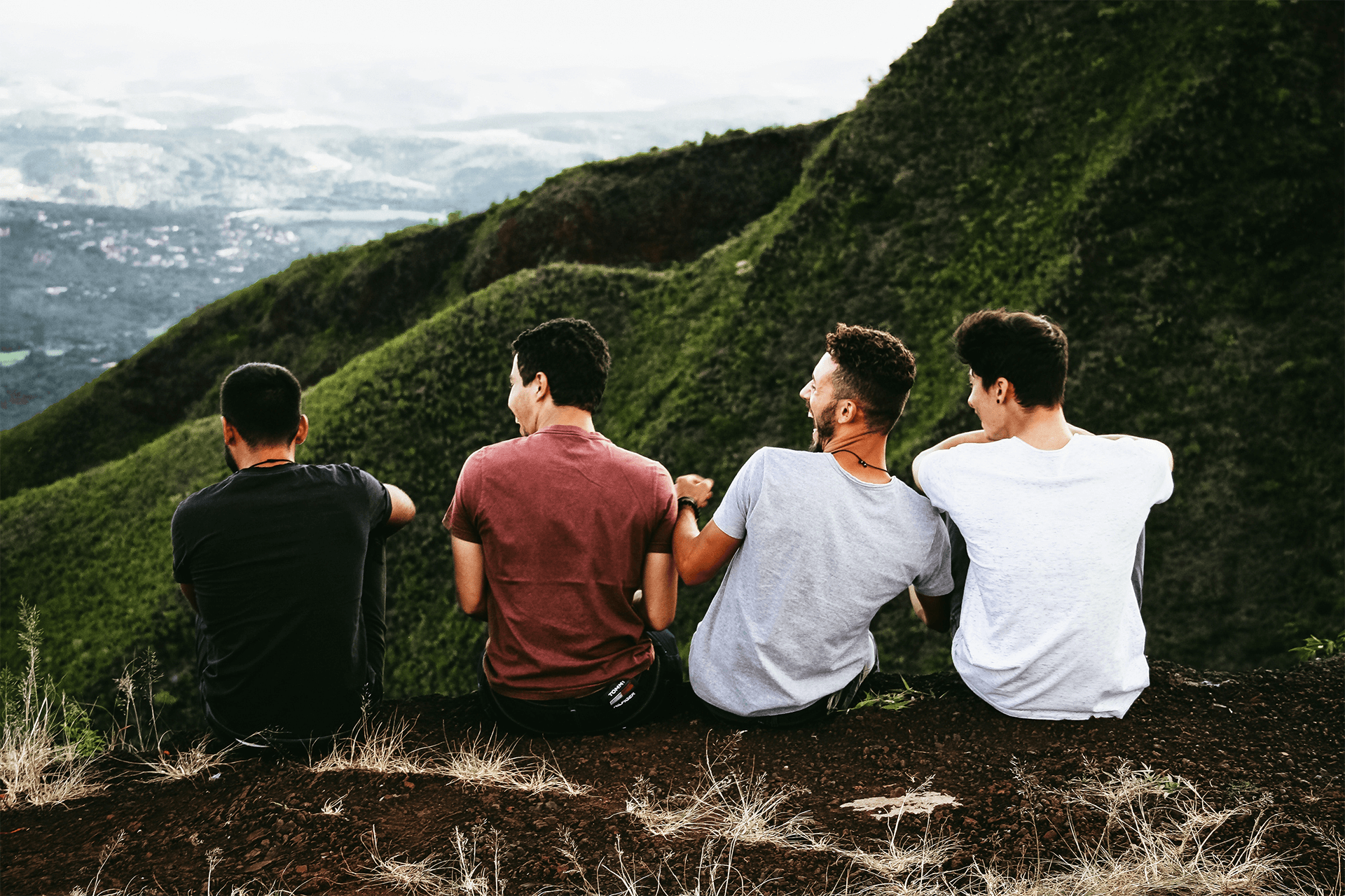 friends sitting on mountainside